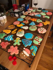 Frosted Christmas cookies in assorted shapes, on rack on top of table